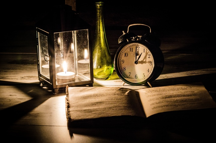 Light shining on Bible with clock